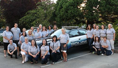 Blue shirted victim advocates group photo in front of Beaverton police vehicle.