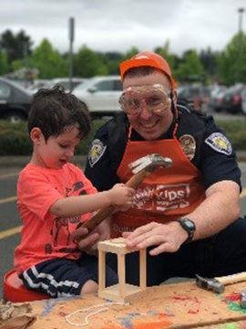 BPD officer, wearing safety goggles, helps young child hammering on a wooden craft project.