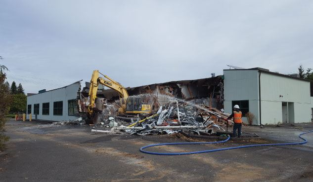 Construction worker hoses down potential toxic debris from old building at Public Safety Center site